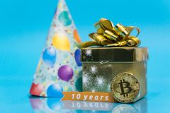 Bitcoin 10 year anniversary, coin with birthday golden present and birthday hat behind it and 10 years sign, copy space. Closeup photo of Bitcoin cryptocurrency stock photography