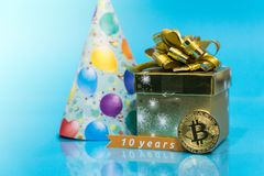 Bitcoin 10 year anniversary, coin with birthday golden present and birthday hat behind it and 10 years sign, copy space. Closeup photo of Bitcoin cryptocurrency stock photo