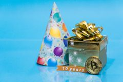 Bitcoin 10 year anniversary, coin with birthday golden present and birthday hat behind it and 10 years sign, copy space stock photography