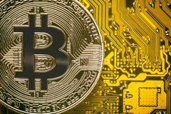 Bitcoin on the yellow computer circuit motherboard close up. Cryptocurrency virtual money background. Stock Photography