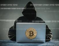 Bitcoin złocista moneta i anonimowy hackera sittign z laptopem obraz royalty free