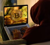 Bitcoin złocista moneta i anonimowy hackera sittign z laptopem obrazy stock