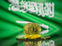 Bitcoin złocista moneta i defocused flaga Arabia Saudyjska tło Wirtualny cryptocurrency pojęcie zdjęcia royalty free