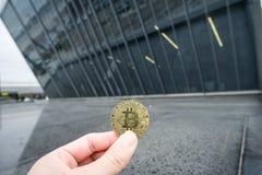 Bitcoin złocista moneta, ręka chwyta bitcoin przed biznesową architekturą obraz royalty free