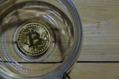 Bitcoin złoto w słoju na drewnianym stołowym tle Oszczędzania lub biznesowy pojęcie zdjęcie royalty free