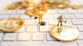 Bitcoin z małą postacią na klawiaturze zdjęcia stock