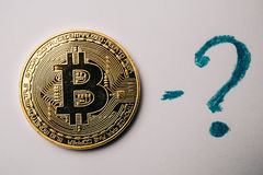 Bitcoin znak zapytania przy białym tłem i moneta obraz stock