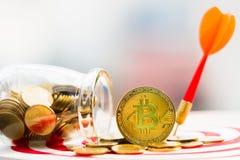 BitcoinBTC金子和击中在掷镖的圆靶的目标中心的箭箭头 免版税图库摄影