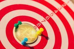 BitcoinBTC金子和击中在掷镖的圆靶的目标中心的箭箭头 免版税库存图片