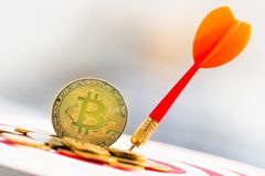 BitcoinBTC Gold and Darts arrow hitting in the target center of dartboard. virtual cryptocurrency concept. royalty free stock image