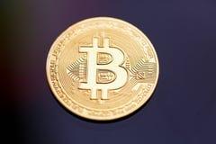 Bitcoinen f?r guld- mynt p? en svart bakgrund arkivfoton
