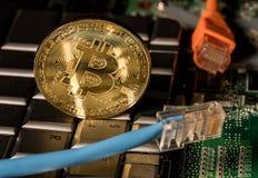 Bitcoinmuntstuk die zich op toetsenbord van computer bevinden Royalty-vrije Stock Afbeeldingen