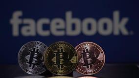 Bitcoinmuntstuk met het Facebook-embleem blauwe scherm stock videobeelden