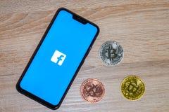 Bitcoinmuntstuk met het Facebook-embleem op het smartphonescherm royalty-vrije stock afbeeldingen
