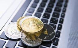 Bitcoinmuntstuk op een bovenkant van andere crypto muntstukken op een toetsenbord van laptop Bitcoin gouden muntstukken Cryptocur Stock Foto's