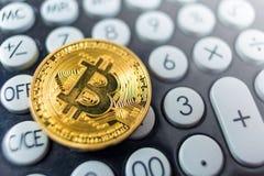 Bitcoinmuntstuk op een calculator stock foto's