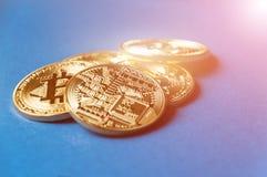 bitcoins几枚硬币在与明亮的焕发的蓝色背景说谎,定调子和弄脏 隐藏货币概念 免版税库存图片