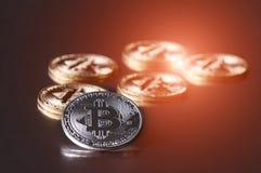 bitcoins几枚硬币在与明亮的焕发的黑暗的背景说谎,定调子和弄脏 隐藏货币概念 图库摄影