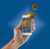 Bitcoins émergeant de l'APP sur le smartphone tenu dans la main Photos libres de droits