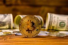 Bitcoins и 100 долларовых банкнот на деревянном столе Стоковое Фото