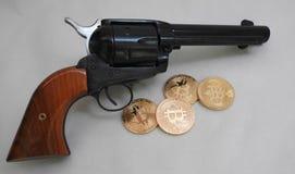 Bitcoins и револьвер Стоковые Изображения