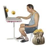 Bitcoins человека минируя на компьютере стоковая фотография
