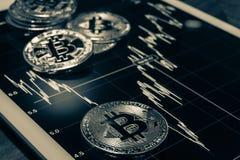 Bitcoins auf der Tablette, welche die Leistungskurve, Schwarzweiss zeigt Stockfotos