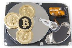 Bitcoins auf einem Festplattenlaufwerk stockbilder