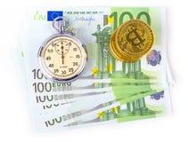 Bitcoins auf einem Stapel von hundert Euros und eine Birne stoppen auf einem wh ab Stockfoto