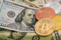 Bitcoins avec des billets de banque des USA, bitcoin d'or, bitcoin argenté, bitcoin en bronze Image libre de droits