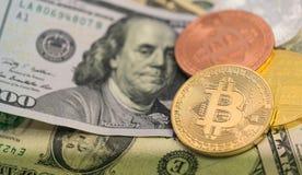 Bitcoins avec des billets de banque des USA, bitcoin d'or, bitcoin argenté, bitcoin en bronze Photographie stock