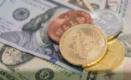 Bitcoins avec des billets de banque des USA, bitcoin d'or, bitcoin argenté, bitcoin en bronze Photos stock
