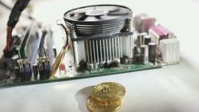 Bitcoins baja abajo cerca de la placa madre de trabajo en a cámara lenta almacen de metraje de vídeo