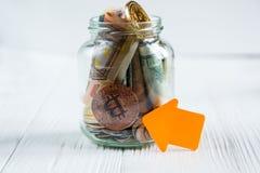Bitcoins brązowa złota moneta w szklanym słoju na białym drewnianym stole Set cryptocurrencies z istnym euro, dolary w słoju zdjęcia royalty free
