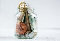 Bitcoins brązowa złota moneta w szklanym słoju na białym drewnianym stole Set cryptocurrencies z istnym euro, dolary w słoju fotografia royalty free