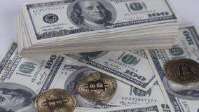 Bitcoins BTC prägt das Drehen mit Rechnungen von 100 amerikanischen Dollar stock footage