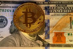 The Bitcoins coin on top of hundred dollars banknote, cryptocurrency accepting for payment and finance concept.  stock photography