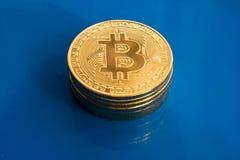 Bitcoins criptos da moeda no fundo de vidro azul Imagens de Stock Royalty Free