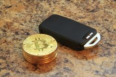 bitcoins cryptocurency with car key on granite table Stock Image