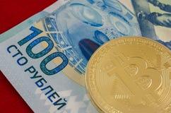 Bitcoins d'or (argent virtuel numérique) et cent roubles Photographie stock libre de droits