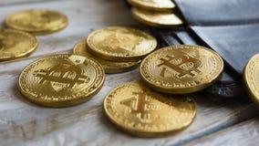 Bitcoins de oro con la cartera de cuero en una tabla de madera Ciérrese encima de vista lateral Imagen de archivo