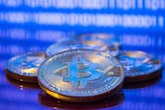 Bitcoins de oro de la foto en fondo digital azul concepto comercial de moneda crypto Imagen de archivo