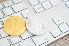 Bitcoins de oro y de plata en un teclado Foto de archivo libre de regalías