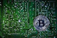 Bitcoins de plata en el microprocesador El fondo verde Cripta de la seguridad imágenes de archivo libres de regalías