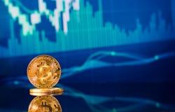 Bitcoins dell'oro con il grafico del grafico del bastone della candela ed il fondo digitale fotografia stock libera da diritti