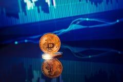 Bitcoins dell'oro con il grafico del grafico del bastone della candela ed il fondo digitale immagini stock libere da diritti