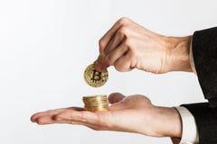 Bitcoins della tenuta della mano dell'uomo d'affari Immagini Stock