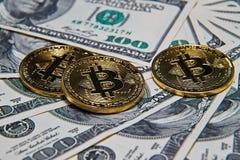 Bitcoins and 100 dollar bills. Golden bitcoins and 100 dollar bills at office desk, macro shot Royalty Free Stock Photos