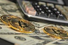 Bitcoins and 100 dollar bills. Golden bitcoins and 100 dollar bills at office desk, macro shot Stock Photos