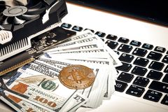 Bitcoins with dollar bills on laptop keyboard. Bitcoin. New virtual money. Video card, concept of mining. Royalty Free Stock Photos